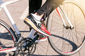 Close-up of male wearing jeans and wearing sport shoes rides bicycle on the park
