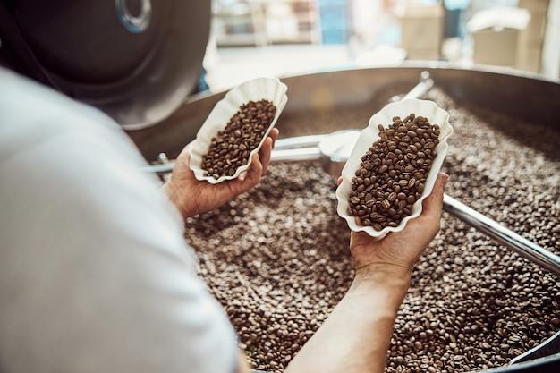 茶色のアラビカコーヒー豆の2つのボウルを保持している男性労働者の手のクローズアップ