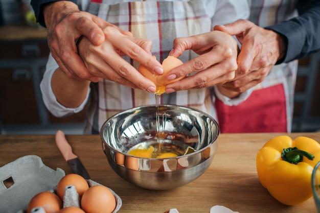 一緒に卵を割る男と女の手のクローズアップ。