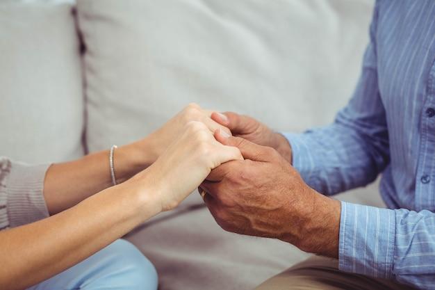 Крупный мужчина и женщина, держась за руки в домашних условиях