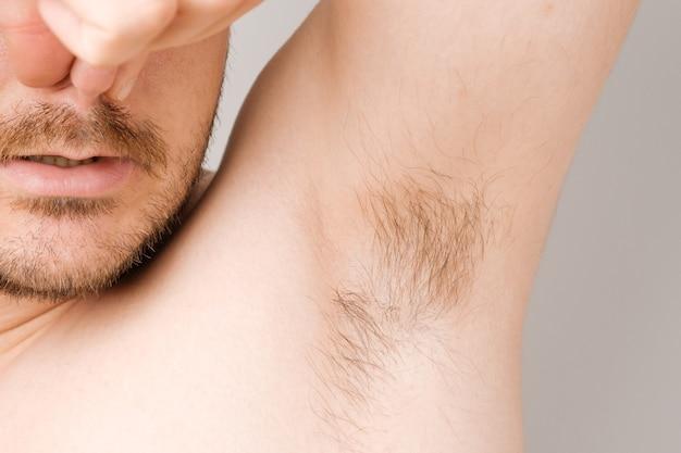 長い剃っていない髪と汗まみれの悪臭から鼻をつまんでいる男の脇の下のクローズアップ