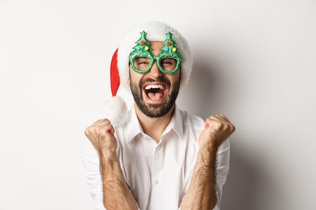 Крупный план человека, празднующего рождество или новый год, в очках для рождественской вечеринки и шляпе санта-клауса, радуясь и крича от радости, стоя
