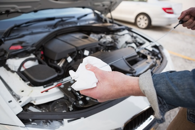 Закройте человека, проверяющего моторное масло автомобиля