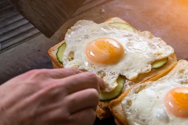 男シェフのクローズアップは、トーストしたパン、目玉焼き、キュウリ、肉、チーズ、トマトの2つの新鮮なサクサクサンドイッチを金属表面にあります