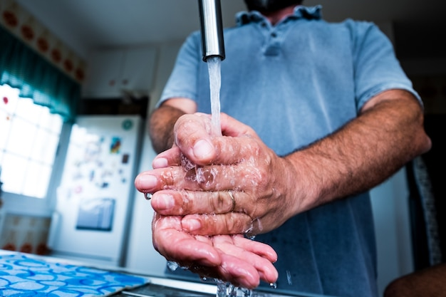 세균과 박테리아를 죽이기 위해 부엌에서 청소하고 손을 씻는 남자의 클로즈업 - covid-19, 코로나바이러스 또는 모든 유형의 질병이나 독감 예방