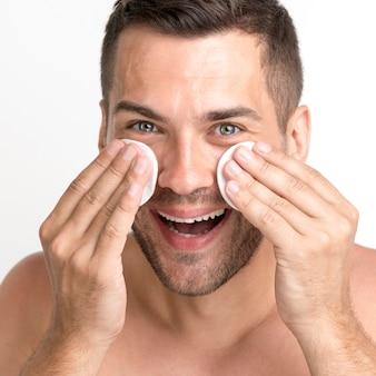 Крупный мужчина чистит лицо ватным тампоном и улыбается