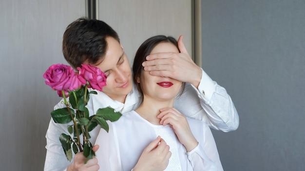Мужчина закрывает глаза своей подруги, чтобы сделать сюрприз, и дарит розу.