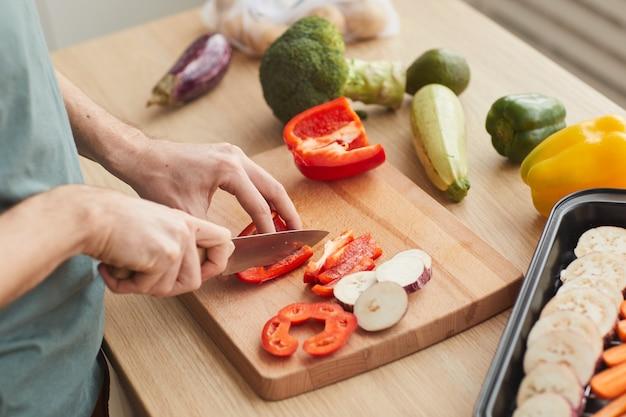 Крупный план человека, режущего свежие овощи на разделочной доске на кухне