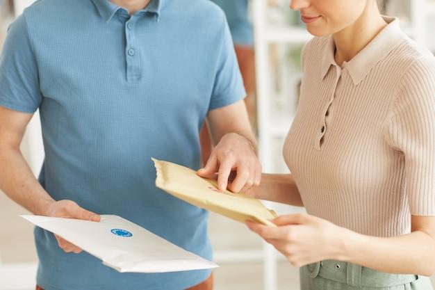 Крупный план мужчины, доставляющего письма молодой женщине дома