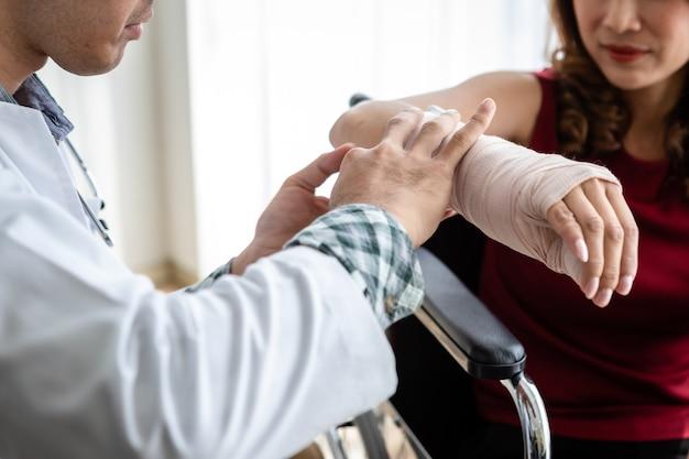 女性患者の腕にラッピングナース包帯スプリントを備えた男性医師のクローズアップは、部屋の病院の背景でより良い治癒のためにアナログ圧力計を備えたアームスプリントを着用します。