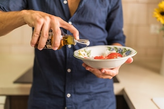 Close-up of man dressing the salad with olive oil in the bowl