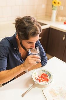 Крупный план человек, стакан воды в кухне