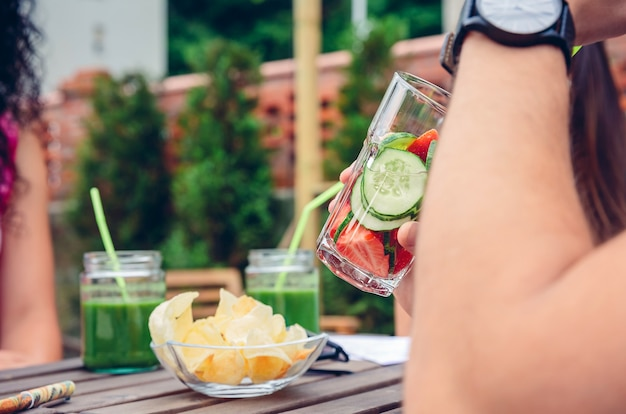 緑の野菜のスムージーと注入されたフルーツウォーターカクテルを飲む男のクローズアップ