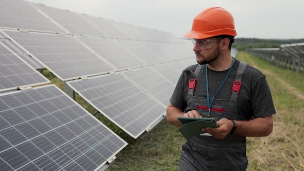 작업복을 입은 남성 엔지니어가 디지털 태블릿을 들고 태양 전지판 설치를 확인하는 재생 에너지 스테이션을 걸어갑니다. 과학 기술. 생태 개념입니다.