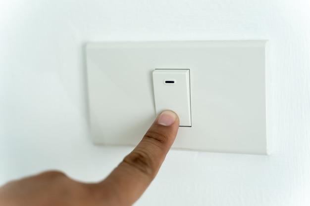 남자 손가락의 클로즈업은 전등 스위치를 켜거나 끕니다.