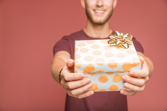 Close-up of man giving gift box with golden bow