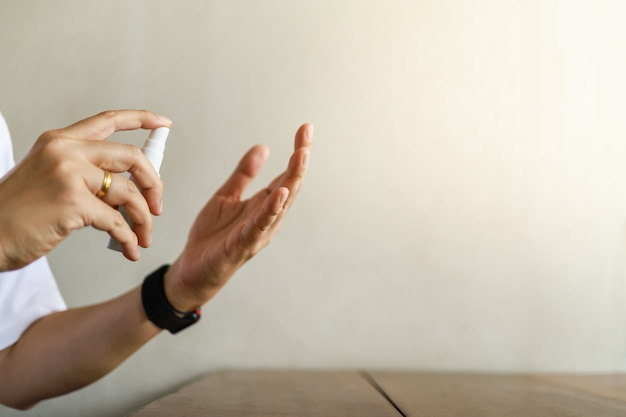 アルコール70%スプレーのミニボトルを押しながら使用する人間の手のクローズアップ