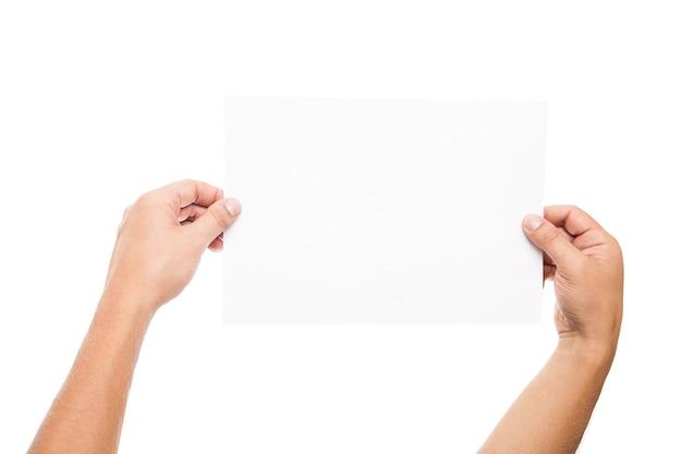 白で空白の広告カードを持っている男の手のクローズアップ