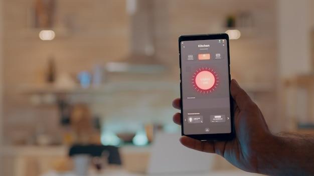 ライトを制御する最新のソフトウェアで携帯電話を持っている男の手のクローズアップ