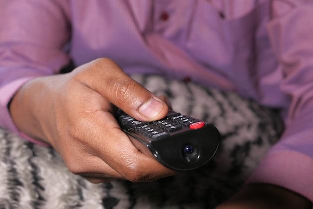 テレビのリモコンを持っている人間の手のクローズアップ。