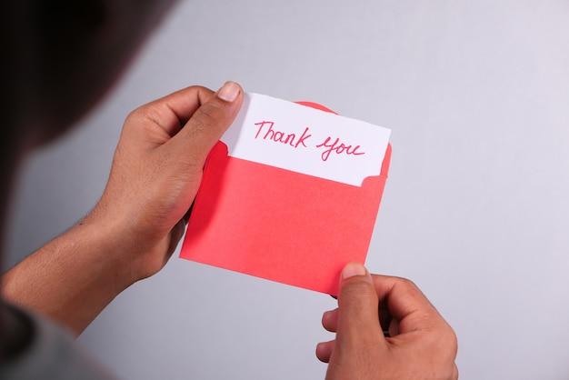 お礼状を読んでいる人間の手のクローズアップ