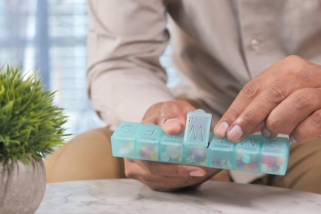 Крупным планом рука человека принимая таблетки из коробки для таблеток