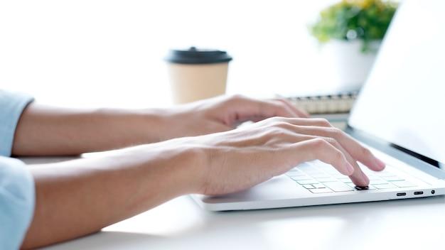 Крупным планом рука человека, печатающего портативный компьютер, работающий в домашнем офисе, онлайн-обучение студента колледжа, обучение, люди и технологии