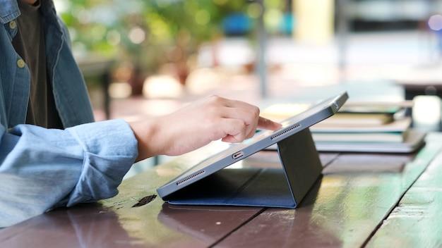 Крупным планом рука человека с помощью цифрового планшета для онлайн-обучения, телекоммуникации