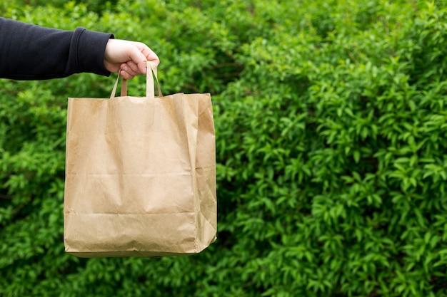 자연 녹색 배경에 테이크아웃 음식을 위한 종이 가방을 들고 남자의 손을 닫습니다. 어떤 날씨에도 고객에게 24시간 배송됩니다.