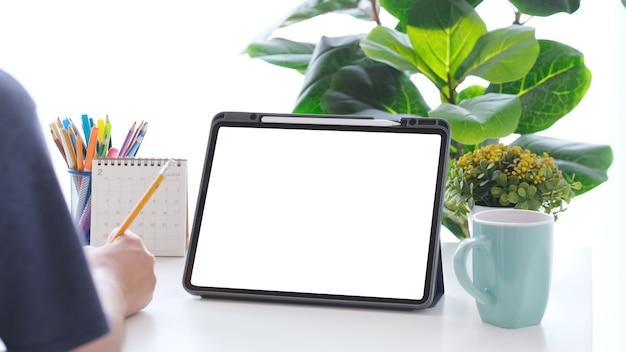 모의 템플릿을 위한 빈 화면 작업 테이블이 있는 사람 손 쓰기 및 디지털 태블릿 닫기