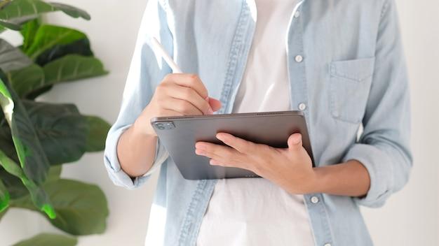 집, 온라인 연구, 통신에서 일하는 동안 디지털 태블릿에 손으로 쓰는 남자의 클로즈업