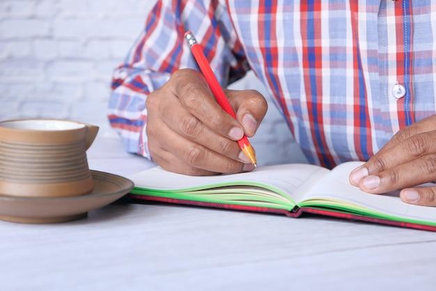 メモ帳に手書きの男のクローズアップ。
