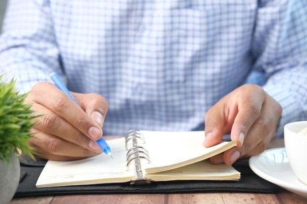 Крупным планом человек почерков на блокноте
