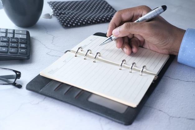 Закройте человек почерков на блокноте.