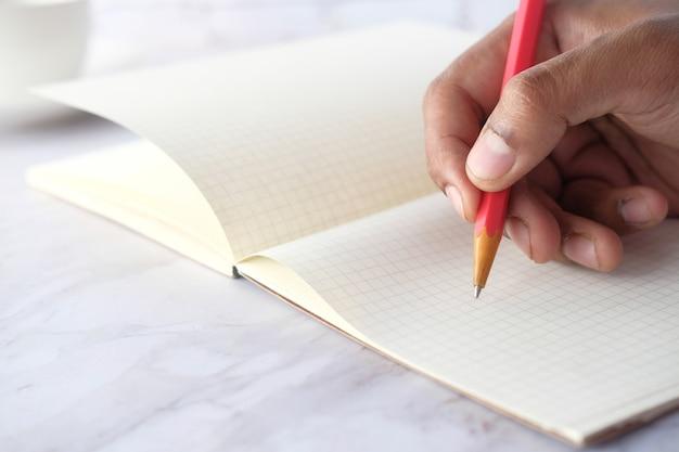 Закройте человек почерков с карандашом на блокноте.