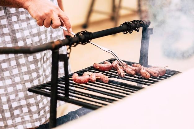 古いスタイルの木と火のバーベキュー バーベキュー グリルで新鮮な肉を調理する男の手のクローズ アップ