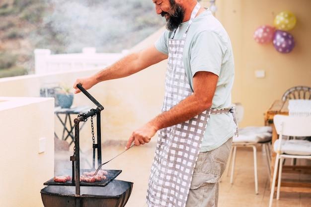 古いスタイルの木材と火のバーベキューバーベキューグリルで新鮮な肉を調理する男の手のクローズアップ