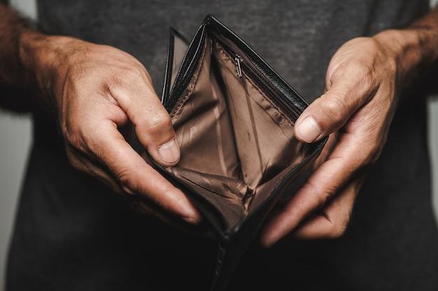 남자 손을 잡고 빈 지갑을 닫습니다. 금융 위기, 파산, 돈 없음, 나쁜 경제 개념.
