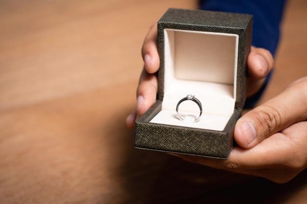Закройте руки человека держа коробку кольца с обручальным кольцом.