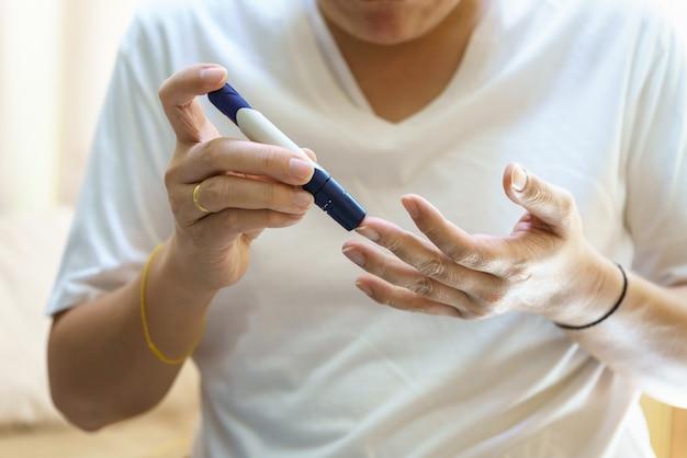 Закройте руки человека, используя ланцет на пальце, чтобы проверить уровень сахара в крови с помощью глюкометра. используйте как понятие медицины, диабета, гликемии, здравоохранения и людей.