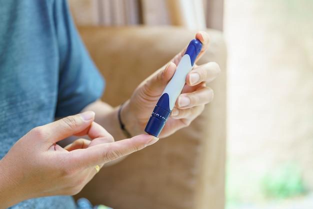 포도당 측정기로 혈당 수치를 확인하기 위해 손가락에 란셋을 사용하여 사람의 손을 닫습니다. 의학, 당뇨병, 혈당, 건강 관리 및 사람 개념으로 사용합니다.