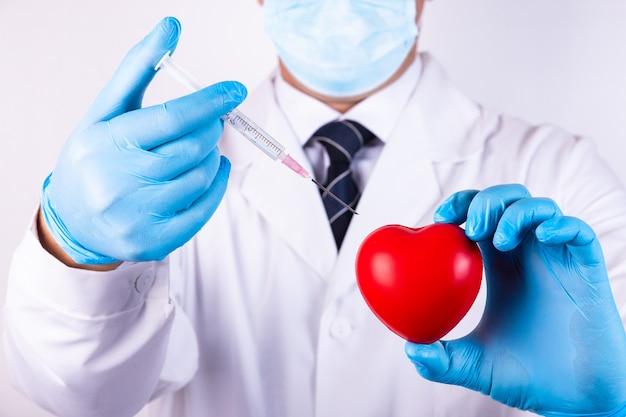 心臓と注射器用の医療用注射器で男の手のクローズアップ