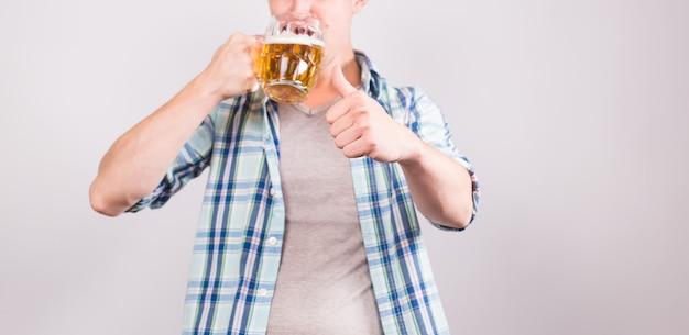 ビールのジョッキを持った男のクローズ アップ。コピー スペースの背景。