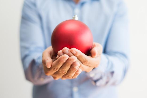 Крупный мужчина держит красивый красный рождественский бал