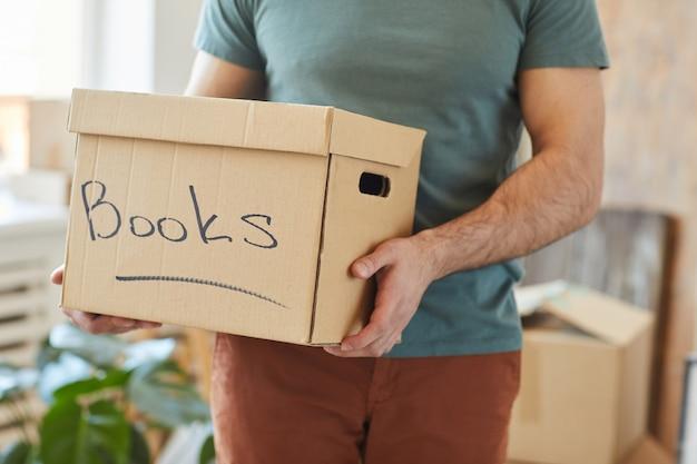 家を移動しながら本と段ボール箱を保持している男のクローズアップ