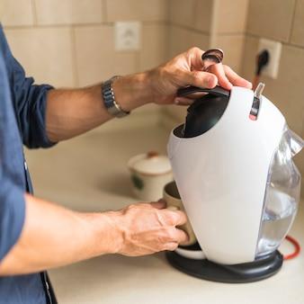 カプセル、エスプレッソコーヒーメーカーでコーヒーマグを持っている人のクローズアップ