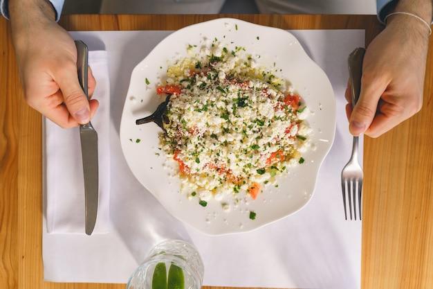 신선한 샐러드와 함께 테이블에 앉아 있는 동안 포크와 나이프를 들고 있는 남자의 클로즈업