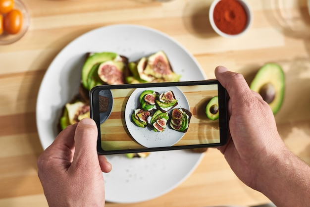 Крупный план человека, держащего мобильный телефон и фотографирующего бутерброды на тарелке со свежими овощами