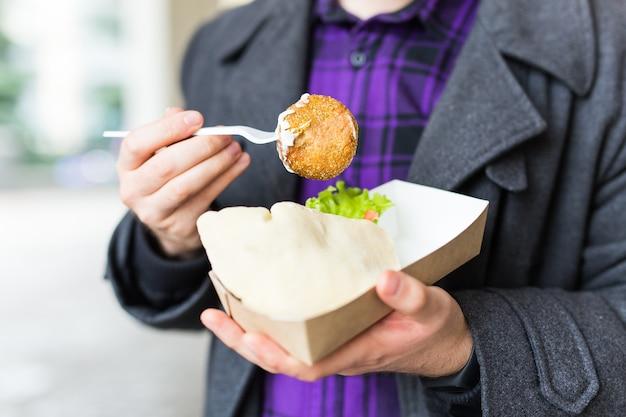 ストリート フード フェスティバルで、ひよこ豆で作った伝統的なおいしいユダヤ料理のファラフェルを使った、1 回限りのプレートを持つ男性の接写。