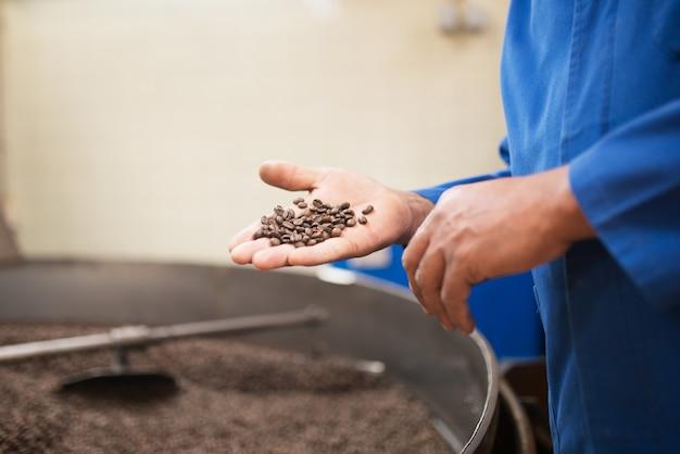 焙煎したコーヒー豆を持っている男のクローズアップ